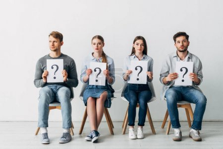 Photo for Group of employees holding cards with question marks while waiting for job interview - Royalty Free Image