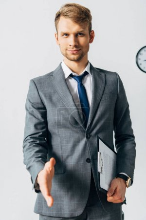 Photo for Selective focus of handsome man with clipboard pulling hand for handshake and looking at camera in office - Royalty Free Image