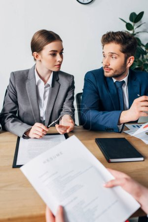 Selective focus of recruiters looking at each other near employee holding resume in office