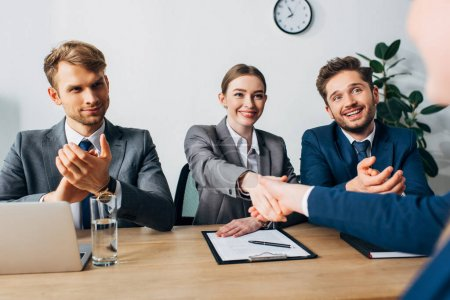 Photo for Selective focus of smiling recruiter shaking hand with employee in office - Royalty Free Image