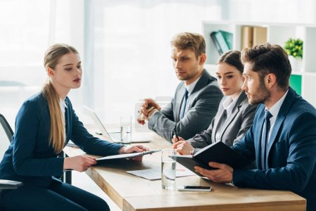 Side view of recruiters looking at employee with clipboard during job interview