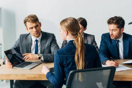 Photo pour Orientation sélective de l'employé regardant un ordinateur portatif lors d'un entretien d'emploi avec des recruteurs dans son bureau - image libre de droit
