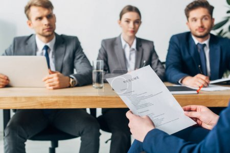 Selective focus of employee holding resume near recruiters at table in office