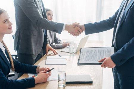 Photo pour Vue latérale de l'employé avec CV serrant la main avec le recruteur pendant l'entrevue d'emploi au bureau - image libre de droit