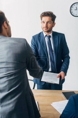 Photo for Selective focus of recruiter with clipboard shaking hands with employee in office - Royalty Free Image