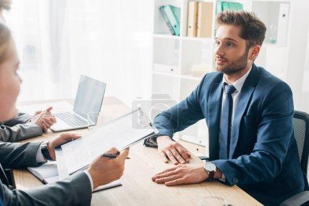 Photo pour Orientation sélective d'un employé regardant un recruteur avec un curriculum vitae pendant un entretien d'embauche - image libre de droit