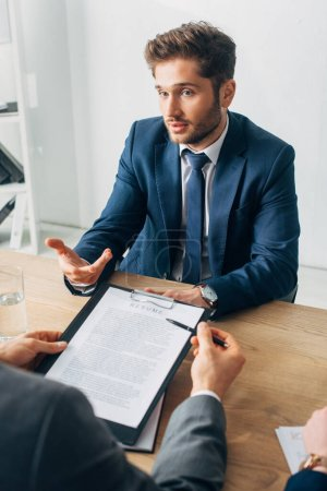 Photo for Selective focus of employee in suit looking at recruiter with resume at table - Royalty Free Image