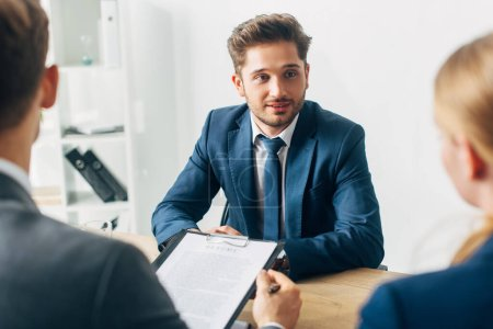 Selective focus of handsome employee looking at recruiter during job interview