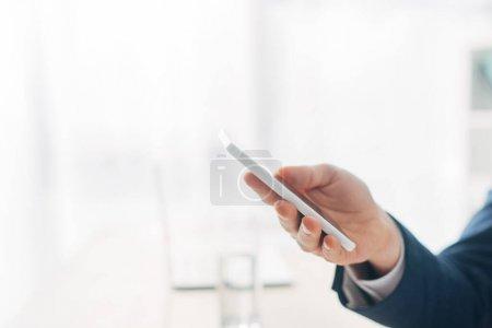Photo pour Vue recadrée de l'homme tenant smartphone avec écran blanc - image libre de droit