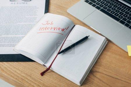 Photo pour Lettrage d'entrevue d'emploi sur ordinateur portable près de CV et ordinateur portable sur la table - image libre de droit