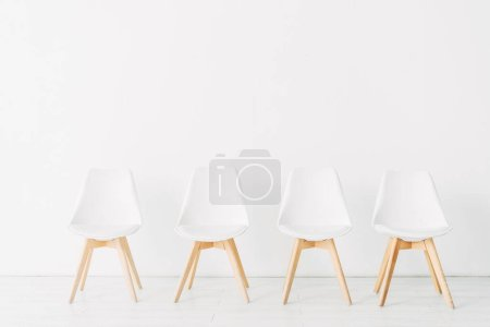 Row of chairs near white wall in office