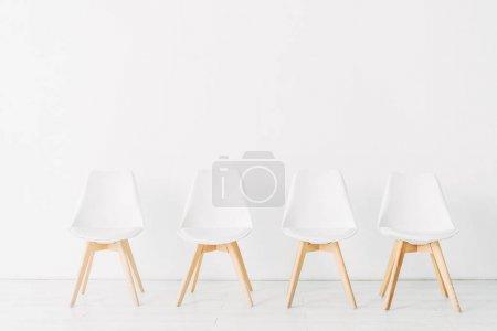 Photo pour Rangée de chaises près du mur blanc dans le bureau - image libre de droit