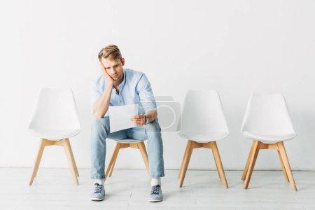 Photo pour Homme fatigué regardant CV tout en étant assis sur la chaise dans le bureau - image libre de droit