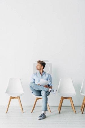 Photo pour Belle employée regardant ailleurs et tenant le CV sur la chaise dans le bureau - image libre de droit