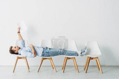 Photo pour Vue latérale de l'employé tenant son CV alors qu'il était allongé sur des chaises au bureau - image libre de droit