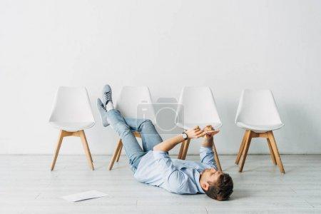 Photo pour Employé utilisant un téléphone intelligent couché sur le sol près d'un curriculum vitae au bureau - image libre de droit