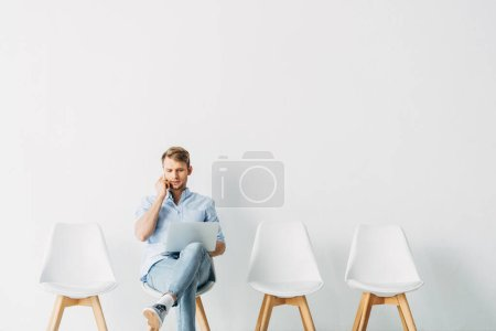 Employee talking on smartphone and using laptop on chair in office