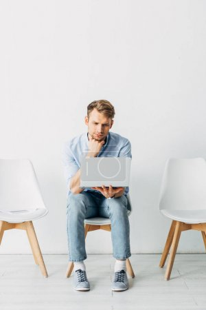 Man using laptop near smartphone and resume on chair in office
