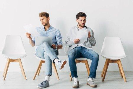 Photo pour Employés avec gadgets et CV en attente d'un entretien d'embauche au bureau - image libre de droit