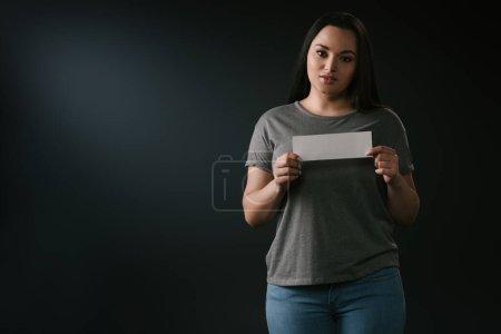 Photo pour Vue de face de plus la taille jolie fille tenant la carte vide sur fond noir - image libre de droit