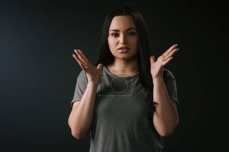 Photo pour Vue de face de la fille irritée plus la taille gestuelle sur fond noir - image libre de droit