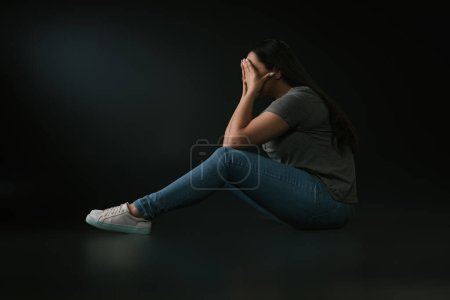 Photo for Side view of crying plus size girl covering face with hands and sitting on black background - Royalty Free Image