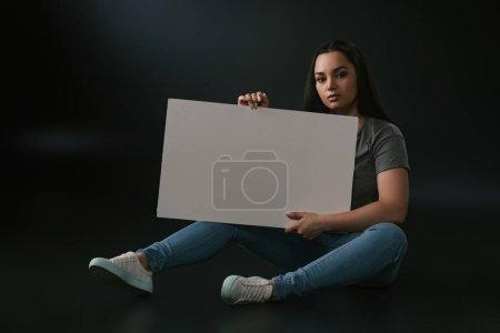 Photo pour Vue de face de grave plus la taille fille assise avec planche vide sur fond noir - image libre de droit