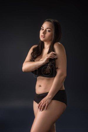 Photo pour Plus la taille fille en sous-vêtements couvrant le corps avec les mains sur fond noir - image libre de droit