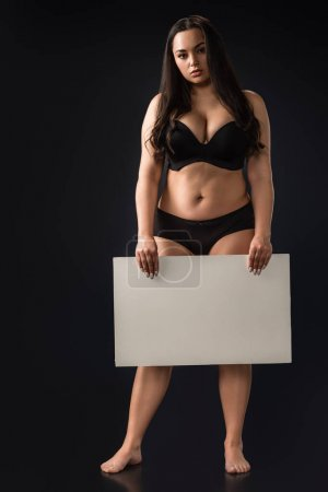 Photo for Front view of full length plus size girl with empty board on black background - Royalty Free Image