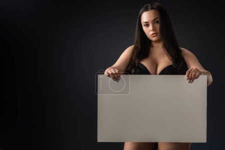 Photo for Beautiful plus size girl in bra with empty board on black background - Royalty Free Image