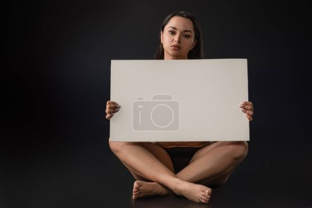 Photo for Front view of plus size girl sitting with crossed legs and holding blank placard on black background - Royalty Free Image