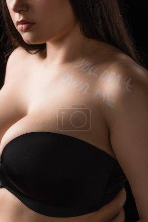 Photo pour Vue recadrée du modèle taille plus en soutien-gorge avec lettrage You Don't Own Me sur le corps isolé sur noir - image libre de droit