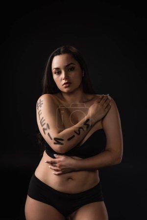 Photo pour Vue de face du modèle plus size en underware noir avec lettrage hashtag féminisme sur le corps isolé sur noir - image libre de droit