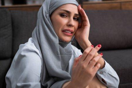Photo pour Femme musulmane bouleversée dans le hijab pleurer dans le salon, concept de violence domestique - image libre de droit