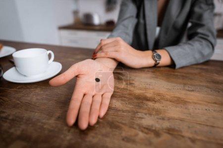 Photo pour Vue recadrée de la femme montrant la main avec un point noir sur la paume près de la tasse, concept de violence domestique - image libre de droit