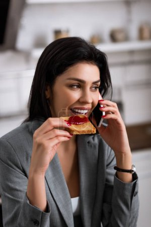 Photo for Happy businesswoman eating toast bread with jam while talking on smartphone and hiding problem of domestic violence - Royalty Free Image