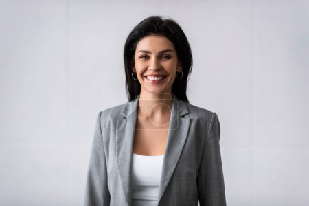 Photo for Cheerful businesswoman smiling while looking at camera on white - Royalty Free Image
