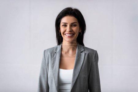 alegre mujer de negocios sonriendo mientras mira a la cámara en blanco