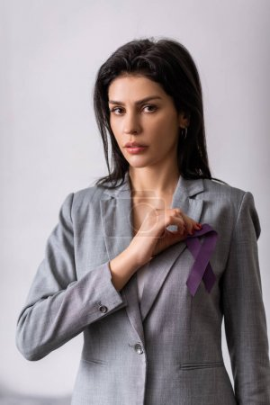Photo for Businesswoman holding purple ribbon on grey, domestic violence concept - Royalty Free Image