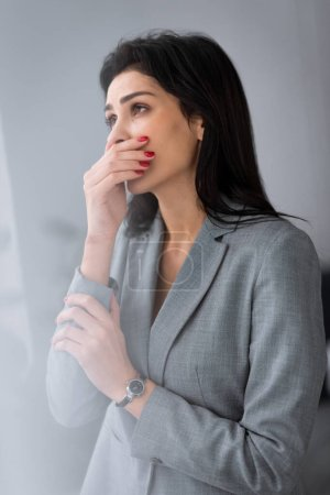 Photo for Frustrated businesswoman with bruise on hand covering mouth, domestic violence concept - Royalty Free Image