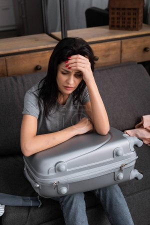 Photo for Depressed woman with bruise on face sitting with suitcase, domestic violence concept - Royalty Free Image