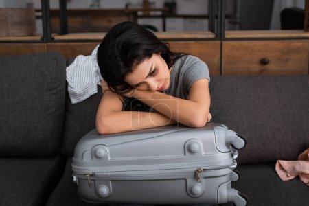Photo for Depressed woman with bruise on face sitting on sofa near suitcase, domestic violence concept - Royalty Free Image