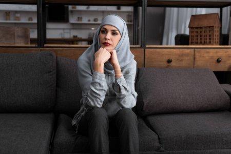 Photo pour Femme musulmane triste dans le hijab assis sur le canapé, concept de violence domestique - image libre de droit