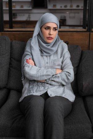 Photo pour Femme musulmane bouleversée dans le hijab assis avec les bras croisés, concept de violence domestique - image libre de droit