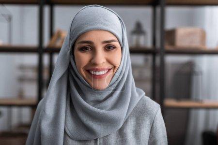 Photo pour Femme musulmane souriante dans le hijab regardant la caméra dans le salon, concept de violence domestique - image libre de droit