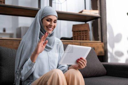 Photo pour Femme arabe positive dans le hijab tenant tablette numérique et agitant la main tout en ayant appel vidéo dans le salon - image libre de droit