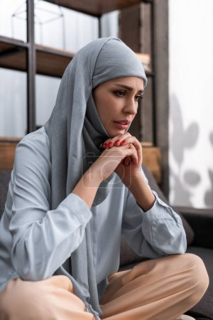 Photo pour Femme arabe inquiète dans le hijab assis avec les mains serrées, concept de violence domestique - image libre de droit