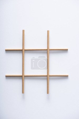 Photo pour Vue du haut de la grille faite de tubes de papier pour jeu d'orteil tic tac sur surface blanche - image libre de droit
