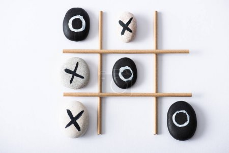Photo for Top view of tic tac toe game with grid made of paper tubes, and pebbles marked with naughts and crosses on white surface - Royalty Free Image