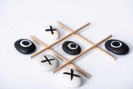 Photo pour Tac tic jeu d'orteil avec grille en tubes de papier et cailloux marqués de nausées et de croix sur surface blanche - image libre de droit